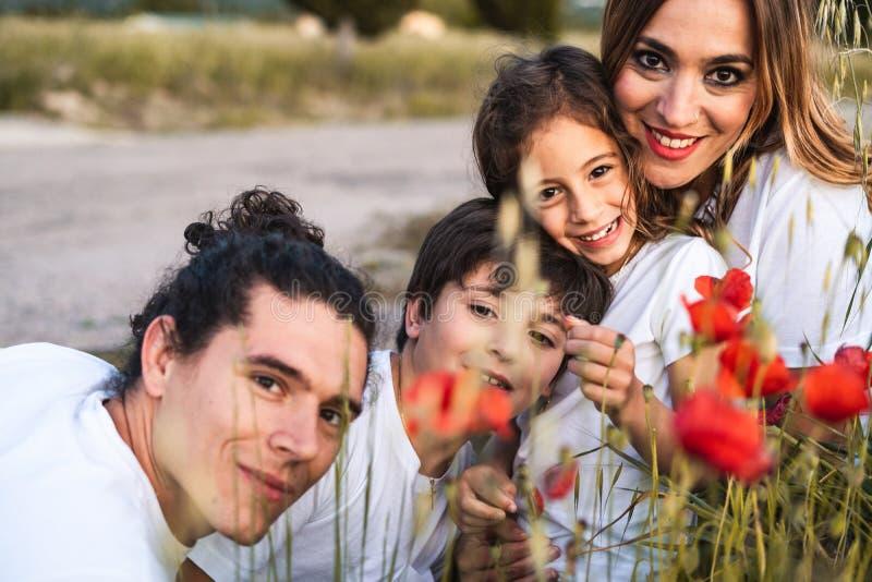 Retrato de uma família nova que sorri e feliz olhando a câmera na parte externa fotos de stock royalty free