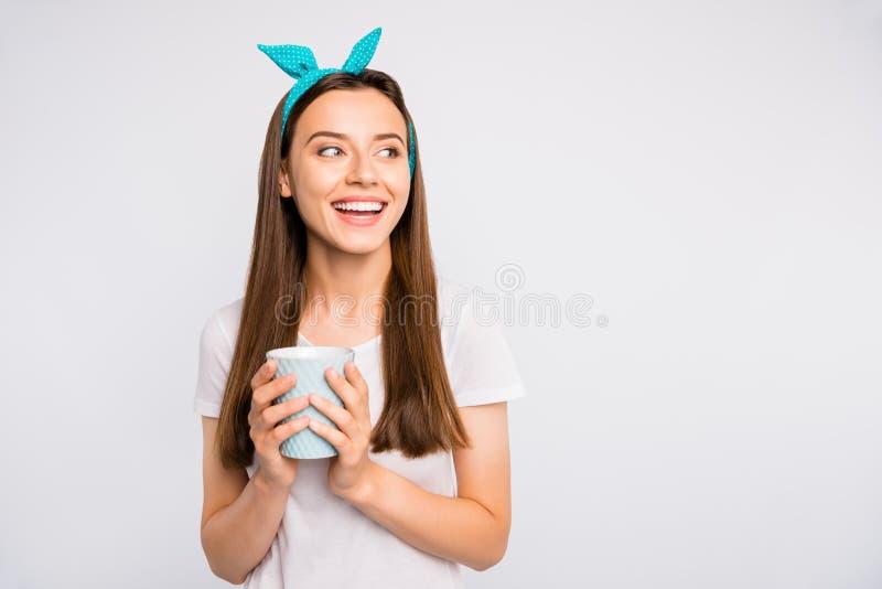 Retrato de uma garota alegre e positiva segurando caneca com bebida de cafeína. Desfrute do descanso, relaxe com os amigos usando imagens de stock royalty free