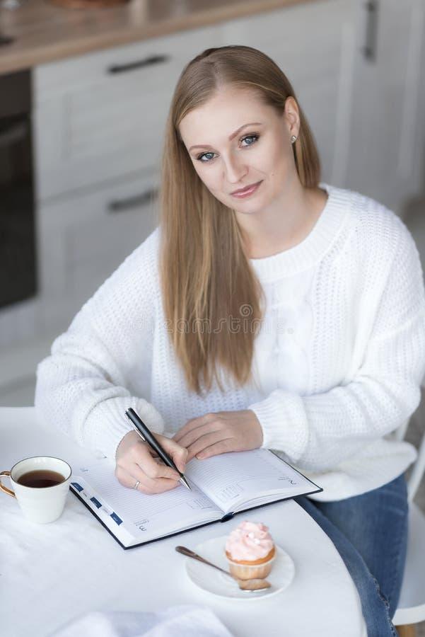 Retrato de uma gravação da menina em um caderno imagens de stock royalty free