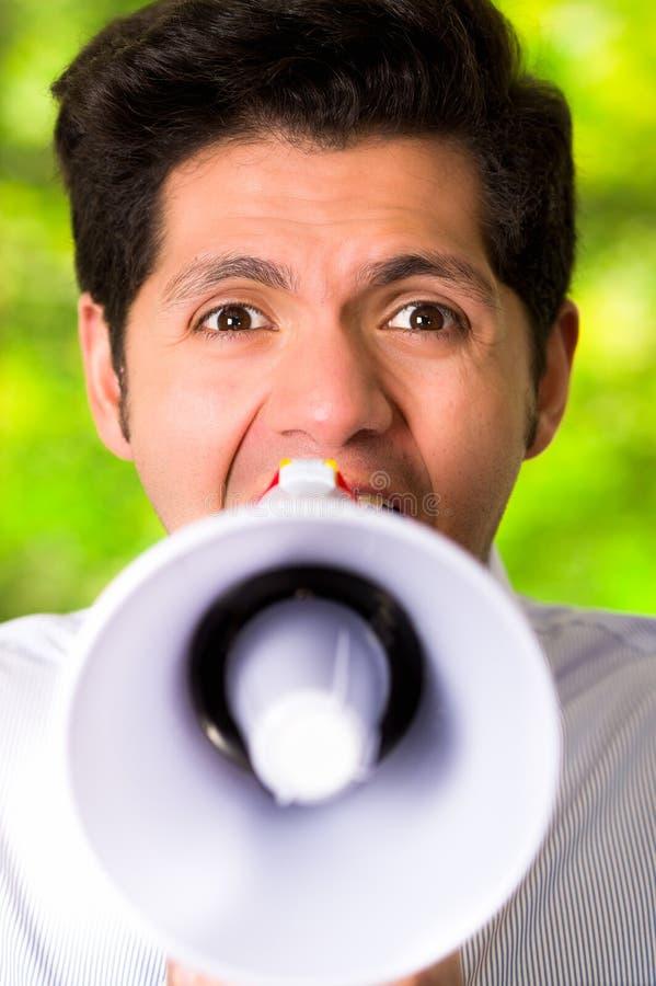Retrato de uma gritaria considerável do homem com um megafone em um fundo verde borrado foto de stock royalty free