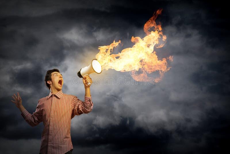 Retrato de uma gritaria do homem novo usando o megafone fotos de stock royalty free
