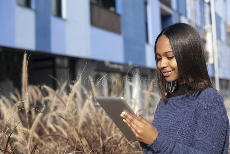 Retrato de uma jovem africana-americana linda que está na rua enquanto usa um telefone celular imagem de stock