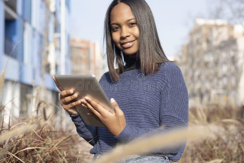 Retrato de uma jovem africana-americana linda que está na rua enquanto usa um telefone celular fotos de stock royalty free