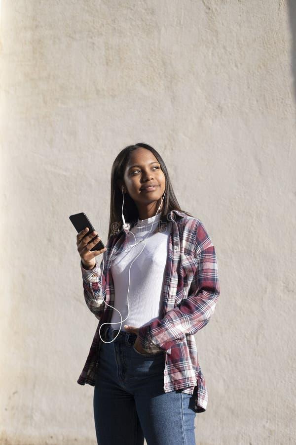 Retrato de uma jovem africana-americana linda que está na rua enquanto usa um telefone celular foto de stock royalty free