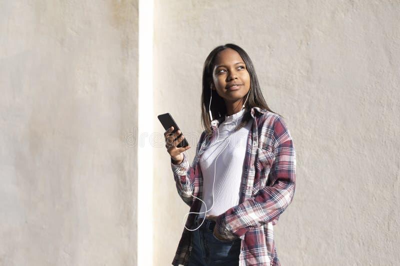 Retrato de uma jovem africana-americana linda que está na rua enquanto usa um telefone celular fotos de stock