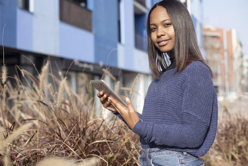 Retrato de uma jovem africana-americana linda que está na rua enquanto usa um telefone celular imagens de stock