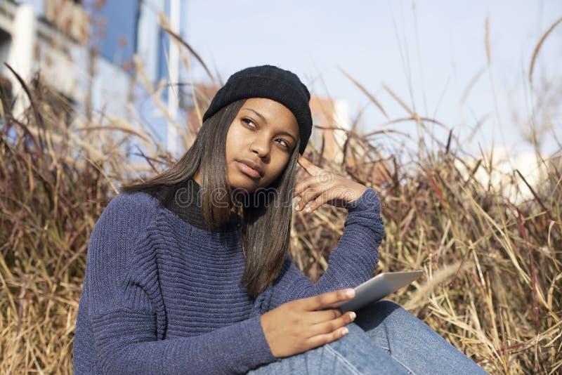 Retrato de uma jovem africana-americana linda usando um chapéu de lã parado na rua enquanto usa um telefone celular foto de stock