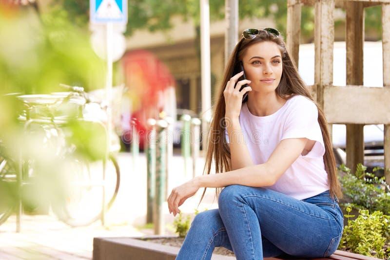 Retrato de uma jovem atraente sentada no banco e falando com alguém no celular foto de stock