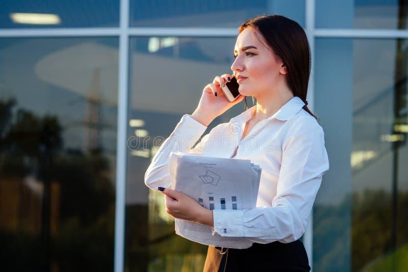 Retrato de uma jovem e bonita mulher indiana empresária com roupas de escritório e papéis conversando ao telefone no escritório imagem de stock royalty free