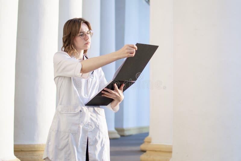 Retrato de uma jovem enfermeira, uma estudante universitária de medicina está de pé com um fonendoscópio e lê um artigo, feliz do foto de stock