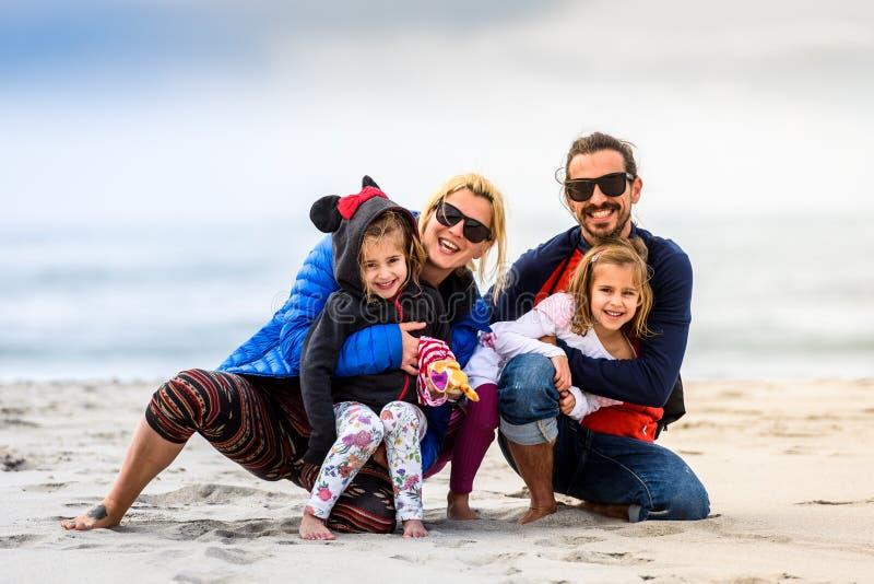 Retrato de uma jovem família feliz posando na praia arenosa foto de stock royalty free