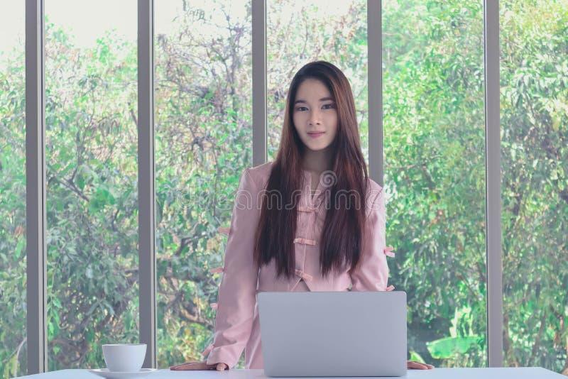 Retrato de uma jovem linda e atraente empresária asiática com um vestido cor-de-rosa a trabalhar no trabalho em escritórios mod imagens de stock royalty free