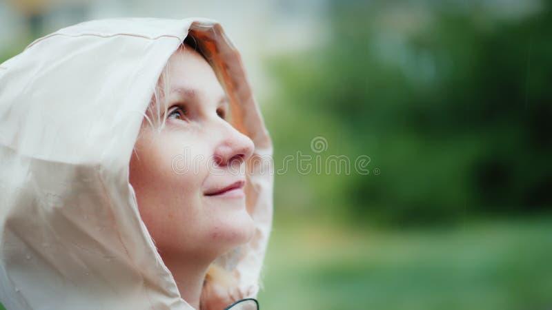 Retrato de uma jovem mulher, apreciando a chuva de mola, olhando acima Caminhada e aventura, conceito do frescor foto de stock