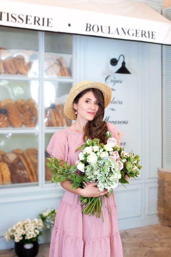 Retrato de uma jovem mulher atrativa em um chapéu do vestido e de palha do verão, mantendo um ramalhete das flores contra um fund fotos de stock royalty free