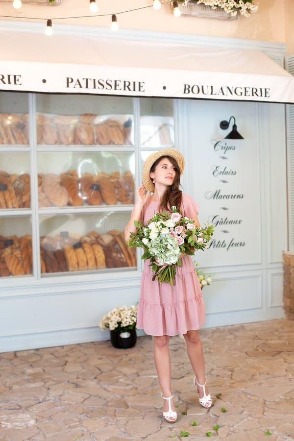 Retrato de uma jovem mulher atrativa em um chapéu do vestido e de palha do verão, mantendo um ramalhete das flores contra um fund fotografia de stock royalty free