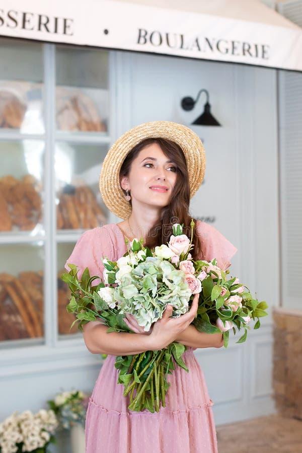 Retrato de uma jovem mulher atrativa em um chapéu do vestido e de palha do verão, mantendo um ramalhete das flores contra um fund imagem de stock