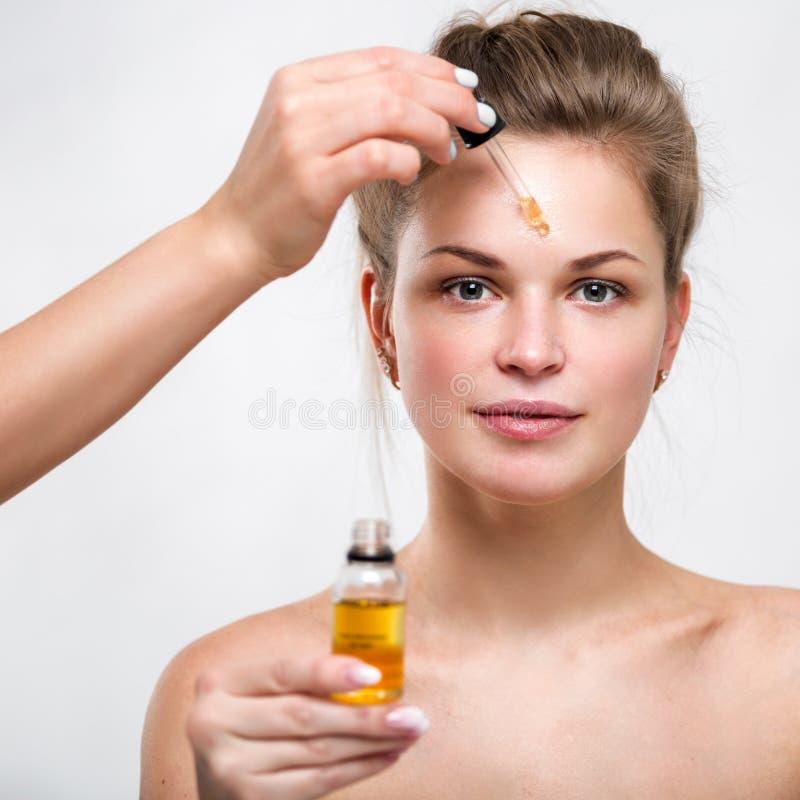 Retrato de uma jovem mulher bonita com óleo facial nas mãos imagens de stock royalty free