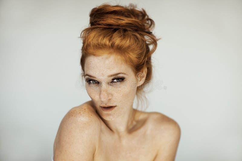 Retrato de uma jovem mulher bonita com cabelo encaracolado e as sardas vermelhos longos imagem de stock