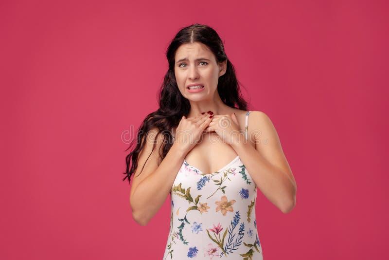 Retrato de uma jovem mulher bonita em uma posi??o clara do vestido no fundo cor-de-rosa no est?dio Emo??es sinceras dos povos fotografia de stock