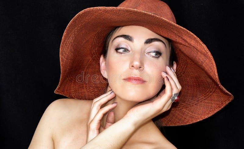 Retrato de uma jovem mulher bonita em um chapéu em um fundo preto fotografia de stock royalty free