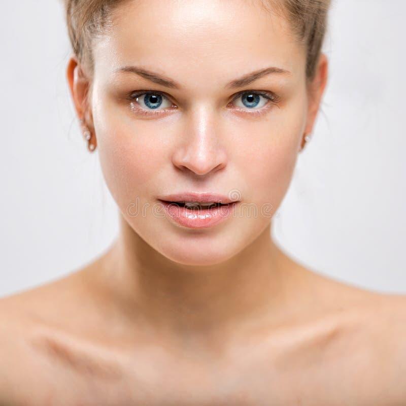 Retrato de uma jovem mulher bonita em um fundo cinzento imagens de stock
