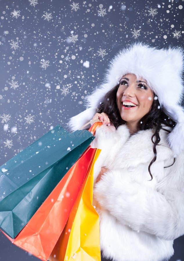 Retrato de uma jovem mulher bonita em uma terra arrendada branca do casaco de pele imagens de stock