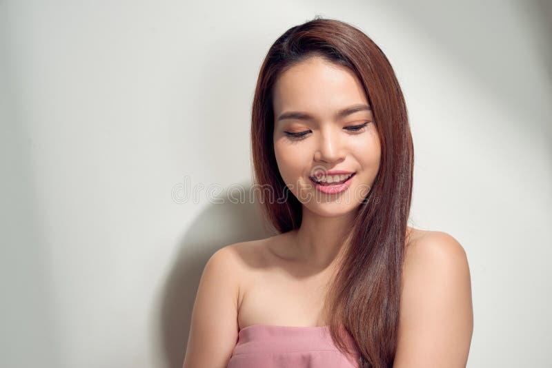 Retrato de uma jovem mulher bonita na roupa do verão sobre o fundo branco foto de stock