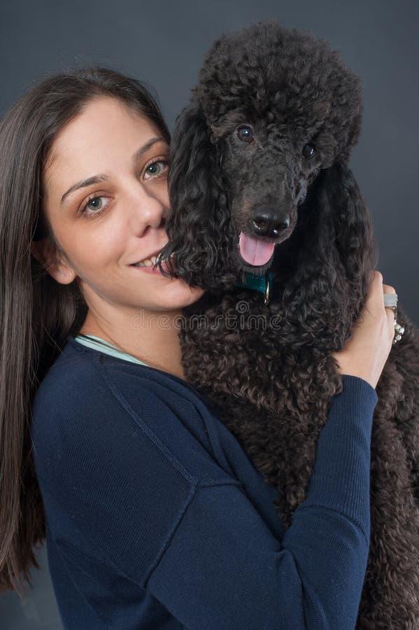 Retrato de uma jovem mulher bonita que abraça seu cão bonito fotografia de stock