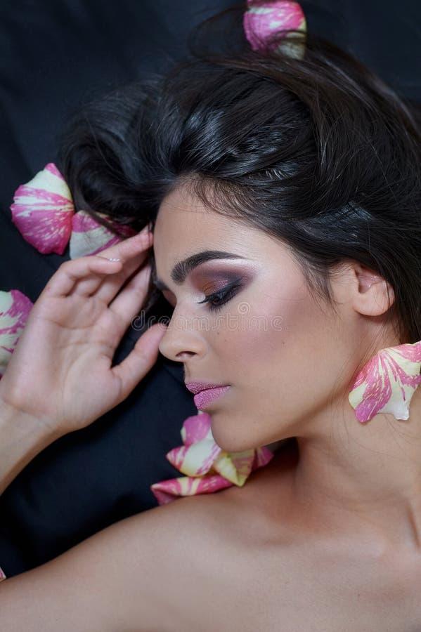 Retrato de uma jovem mulher bonita que coloca nas pétalas cor-de-rosa escassas fotos de stock royalty free