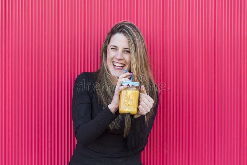Retrato de uma jovem mulher bonita que guarda um jarro saudável de ora imagens de stock