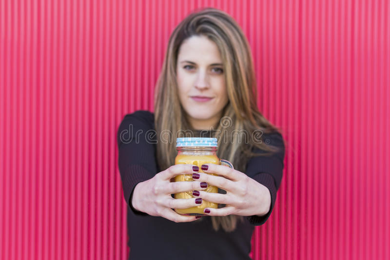 Retrato de uma jovem mulher bonita que guarda um jarro saudável de suco de laranja foto de stock