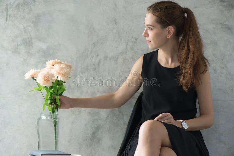 Retrato de uma jovem mulher bonita que relaxa com a flor na sala de visitas imagens do estilo do efeito do vintage fotografia de stock