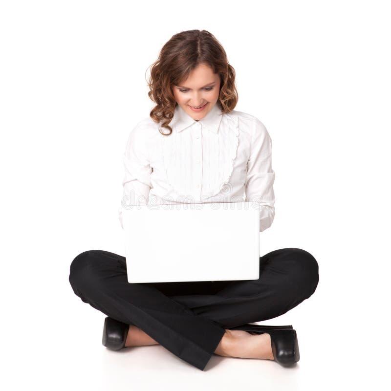 Retrato de uma jovem mulher bonita que senta-se na frente de seu portátil imagem de stock