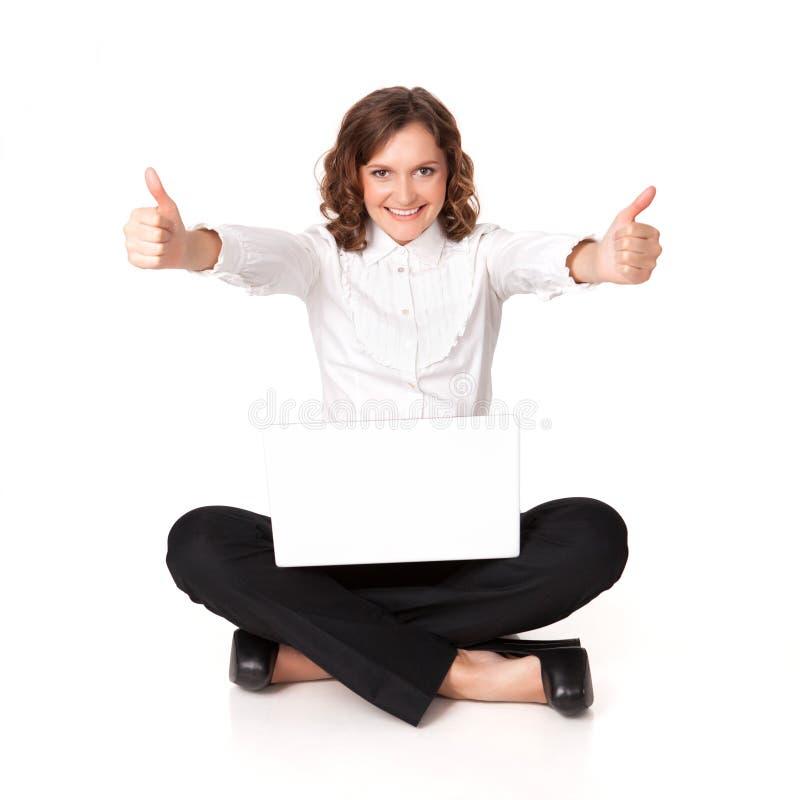 Retrato de uma jovem mulher bonita que senta-se na frente de seu portátil fotografia de stock