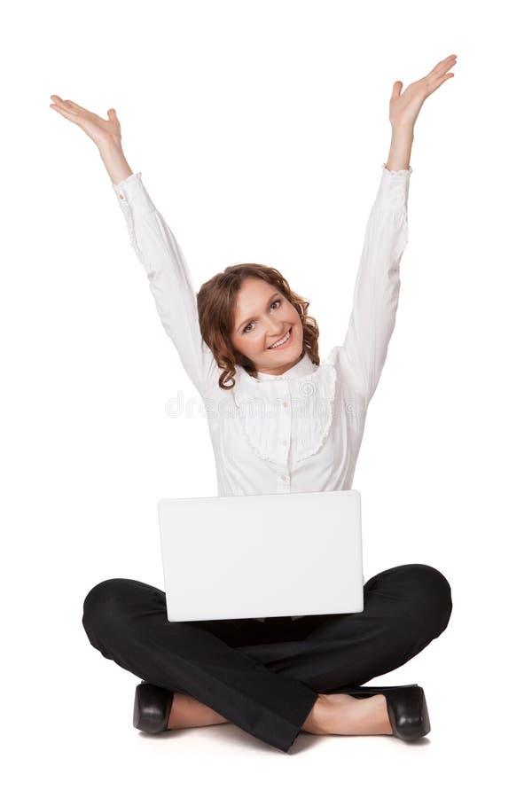 Retrato de uma jovem mulher bonita que senta-se na frente de seu portátil imagens de stock