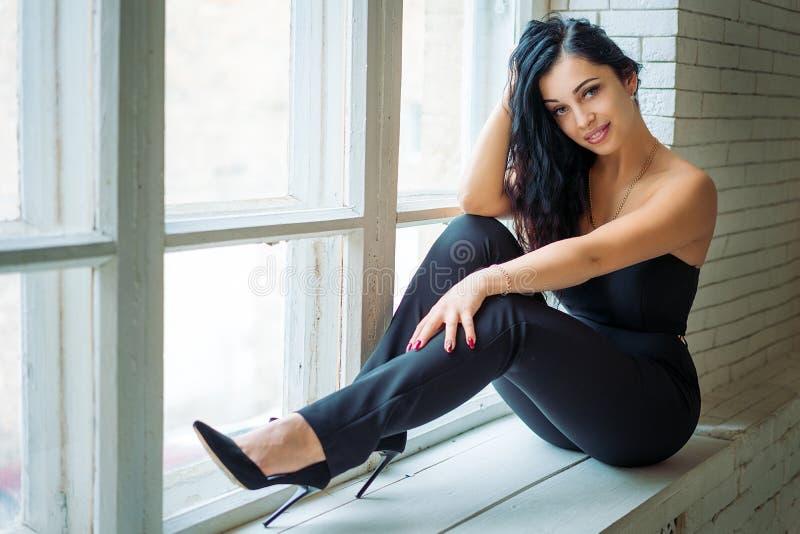 Retrato de uma jovem mulher bonita que senta-se na soleira imagem de stock royalty free