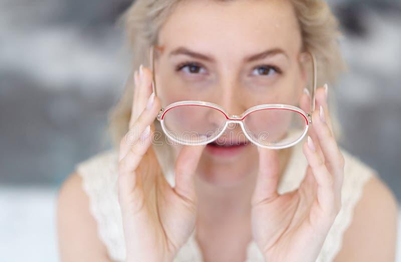 Retrato de uma jovem mulher com os vidros e o cabelo louro que guardam os vidros na frente de sua cara, sua cara fora de foco foto de stock