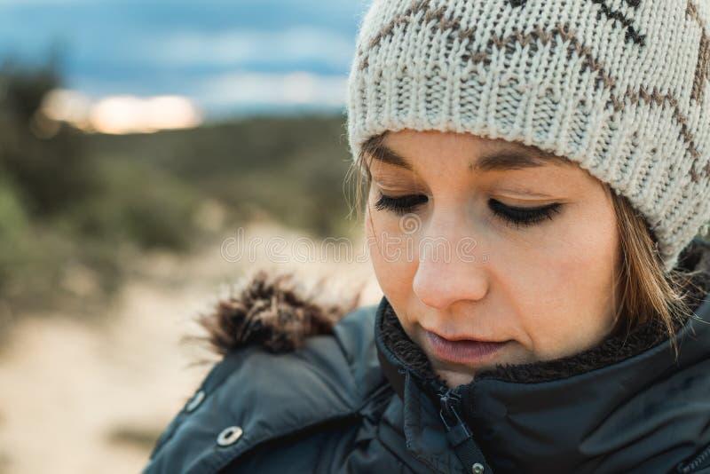 Retrato de uma jovem mulher com um chapéu de lãs e uma expressão séria fotografia de stock royalty free