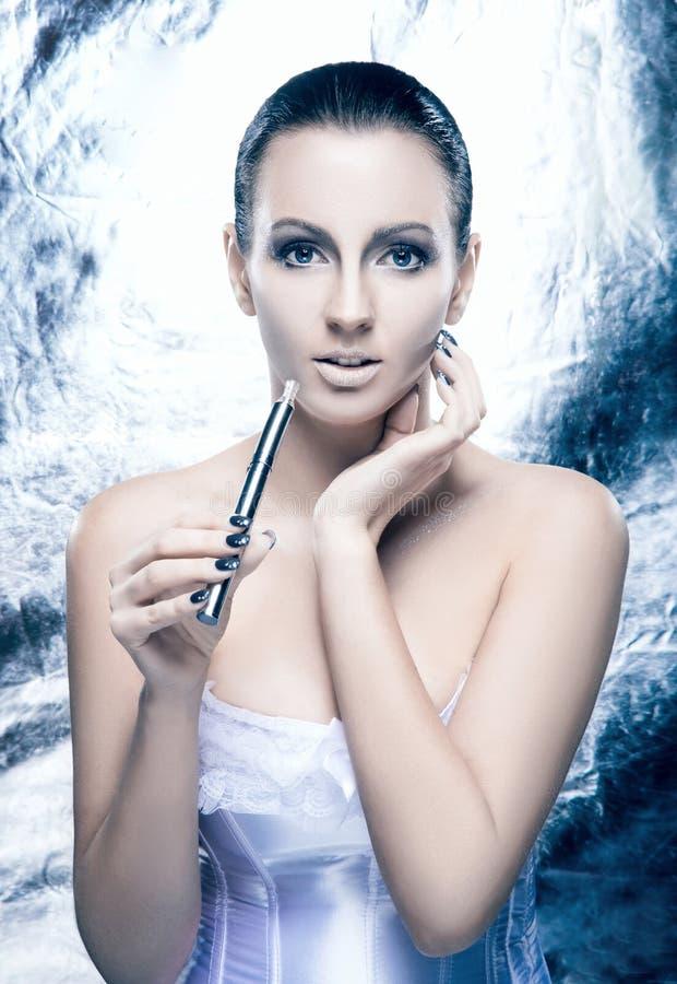 Retrato de uma jovem mulher com um e-cigarro fotografia de stock royalty free