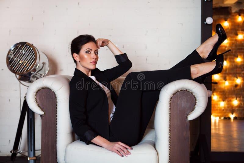 Retrato de uma jovem mulher com um sorriso bonito que senta-se no sofá foto de stock royalty free
