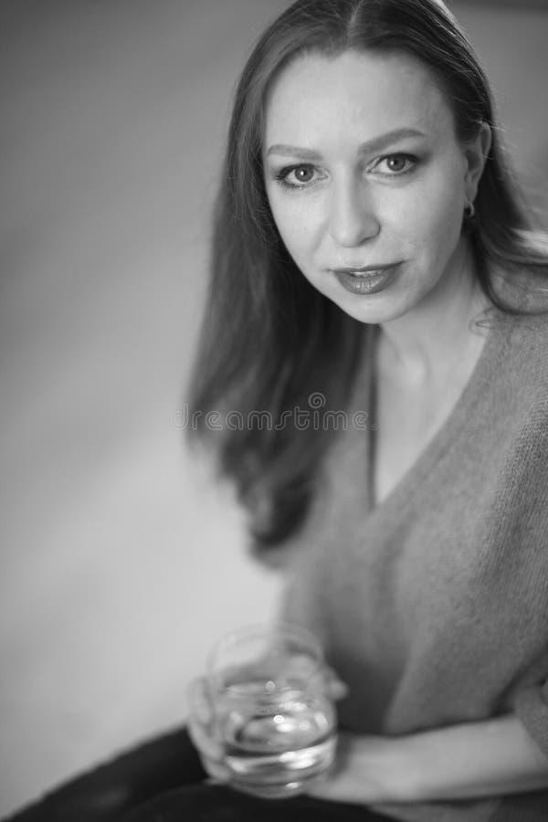 Retrato de uma jovem mulher com um vidro fotografia de stock