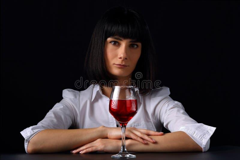 Retrato de uma jovem mulher com um vidro do vinho tinto fotografia de stock royalty free