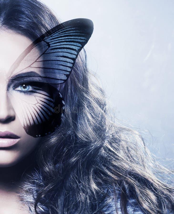 Retrato de uma jovem mulher com uma borboleta em sua cara fotos de stock royalty free