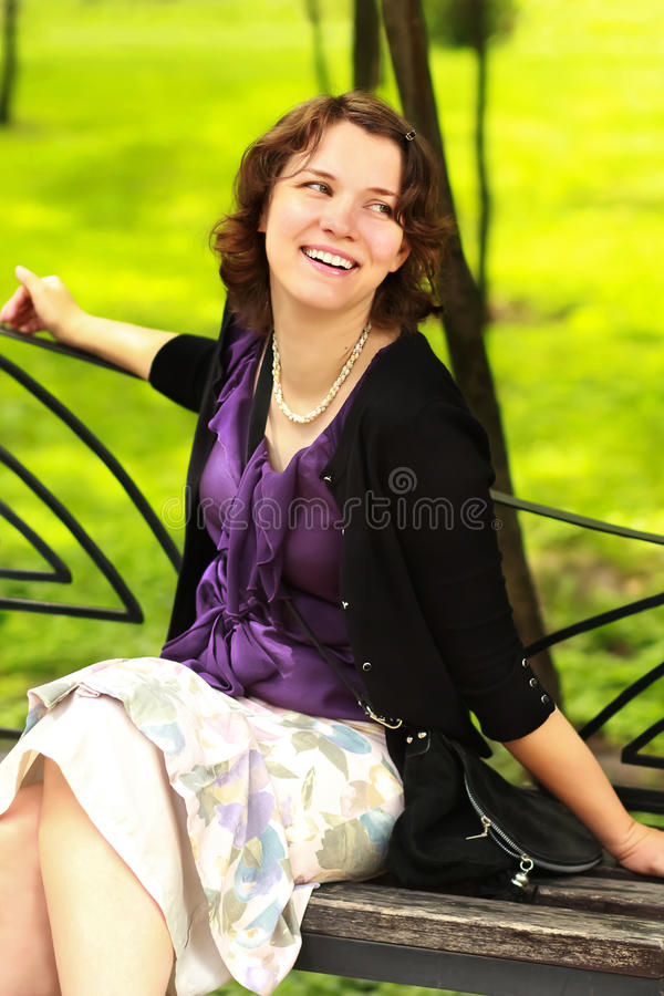 Retrato de uma jovem mulher de sorriso feliz que senta-se no banco no parque imagem de stock royalty free