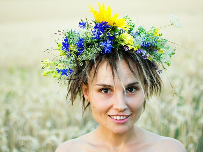 Retrato de uma jovem mulher em uma grinalda de suportes de flores selvagens no campo no por do sol fotografia de stock