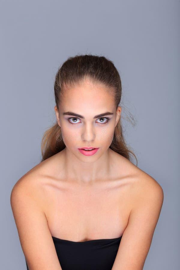 Retrato de uma jovem mulher em uma luz - fundo cinzento, emoções, cosméticos foto de stock