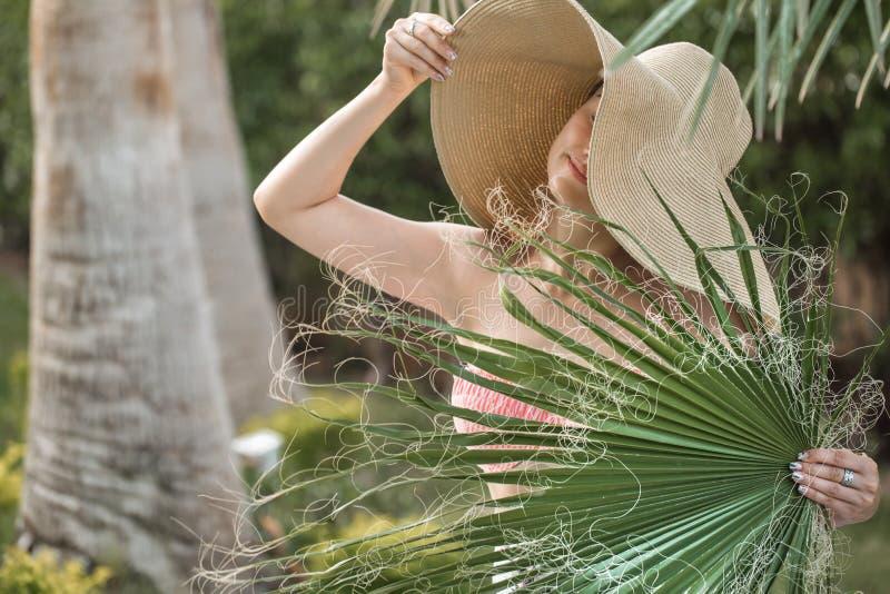Retrato de uma jovem mulher em um chapéu bonito, e folha de palmeira foto de stock royalty free