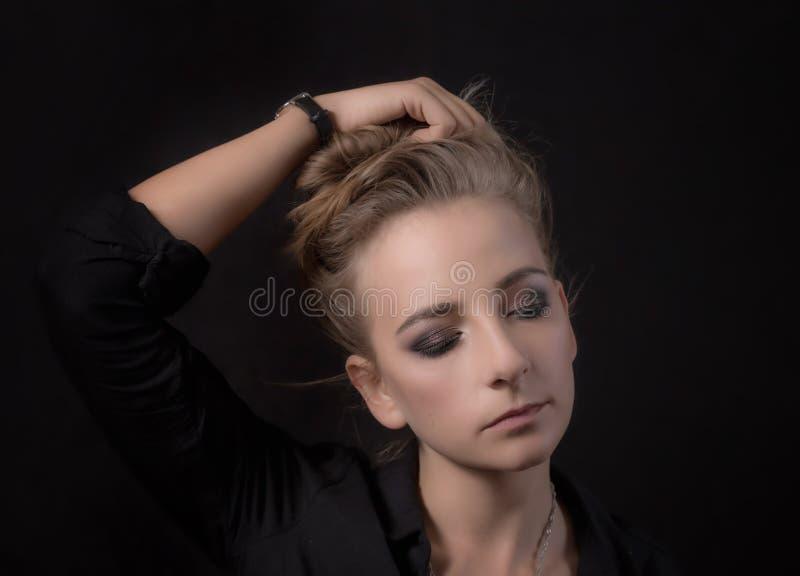Retrato de uma jovem mulher em um preto imagem de stock