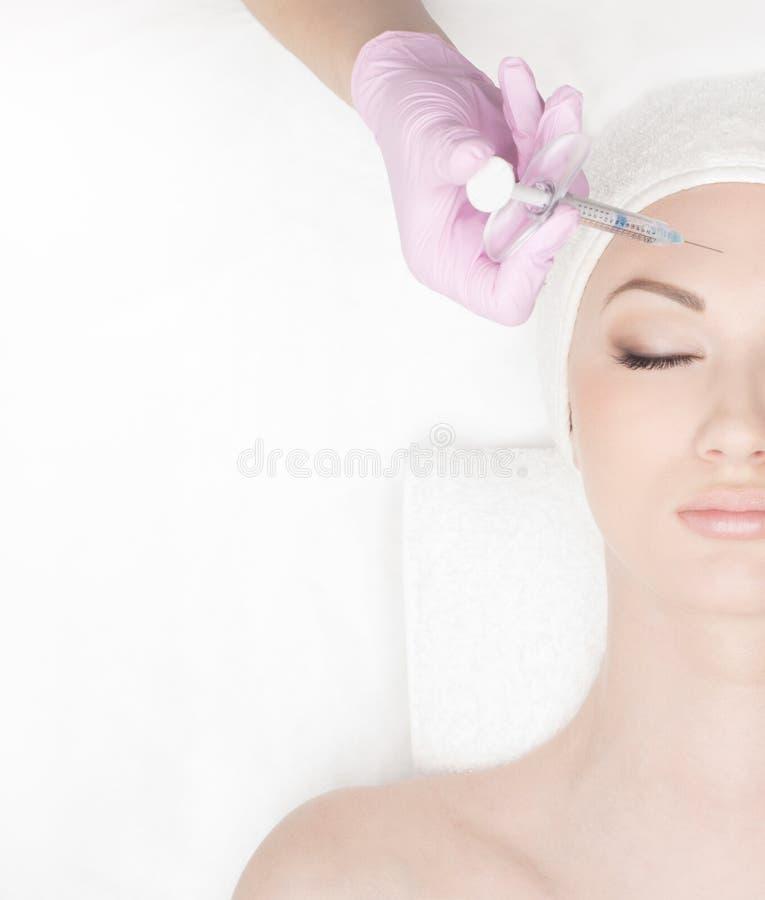 Retrato de uma jovem mulher em um procedimento da injeção do botox fotos de stock