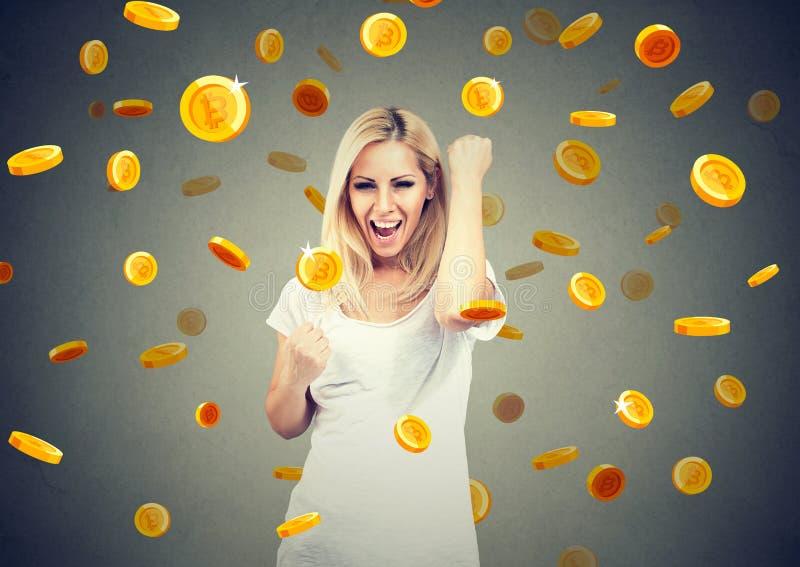 Retrato de uma jovem mulher feliz que comemora o sucesso financeiro sob uma chuva do bitcoin fotografia de stock